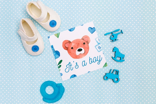 Flat lay of blue baby shower decorations with shoes