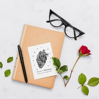 Flat lay of book with glasses and rose