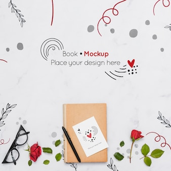 Flat lay of book with roses and glasses
