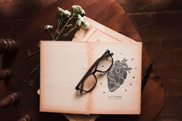 Flat lay of books with glasses and flowers