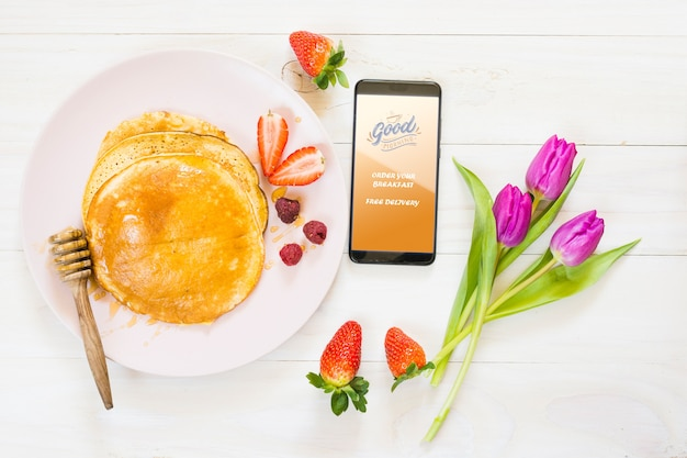 Flat lay breakfast with pancakes next to smartphone