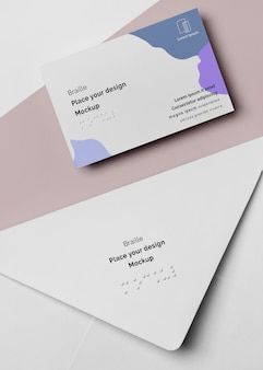 Flat lay of business card with braille in envelope