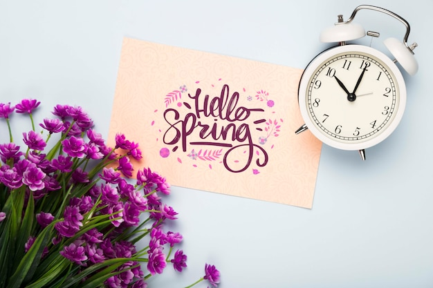Flat lay of card with clock and flowers