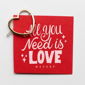 Flat lay of card with heart-shaped golden pin