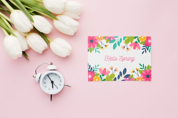 Flat lay of card with tulips and clock