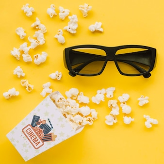 Flat lay of cinema popcorn in cup with glasses