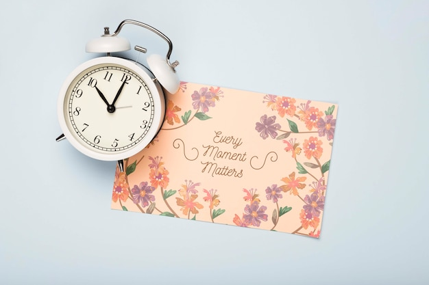 Flat lay of clock and floral card for spring