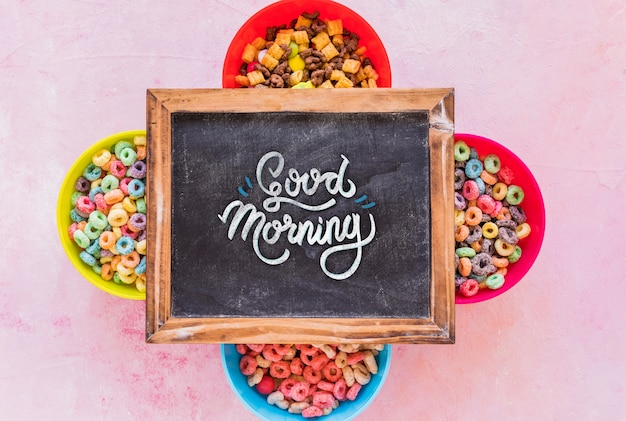 Flat lay of colorful cereals and chalkboard on plain background