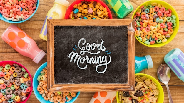 Flat lay of colorful cereals and chalkboard on wooden table