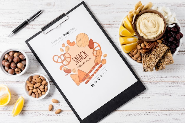 Flat lay composition of snacks with clipboard mock-up
