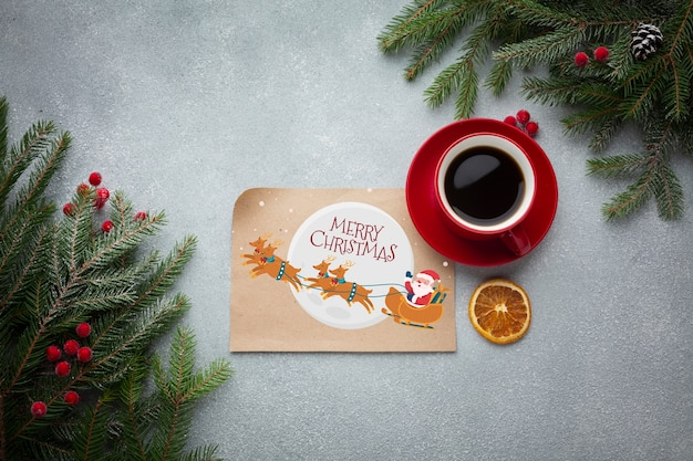 Flat lay cup of coffee with with merry christmas letter and pine leaves