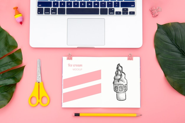 Flat lay of desk surface with laptop and leaves