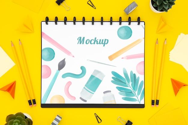 Disposizione piana della superficie dello scrittorio con il taccuino e le matite