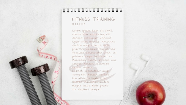 Flat lay of fitness notebook with apple and weights