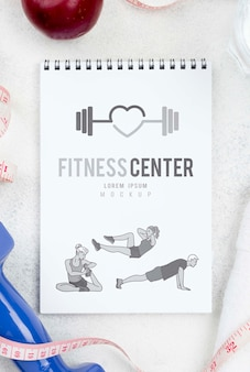 Flat lay of fitness notebook with measuring tape and apple