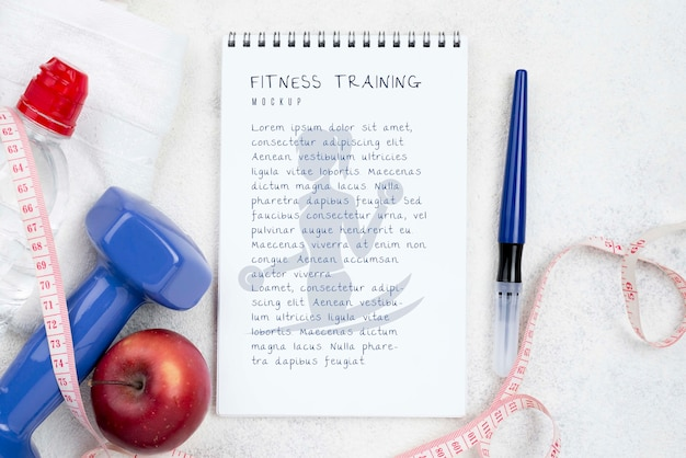 Flat lay of fitness notebook with measuring tape and weight