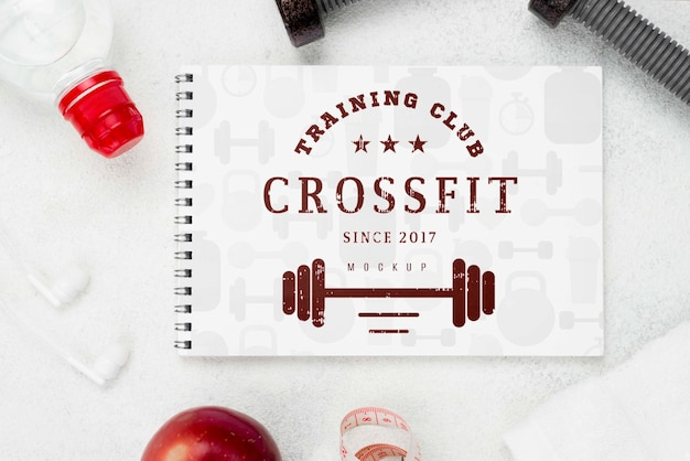 Flat lay of fitness notebook with weights and apple
