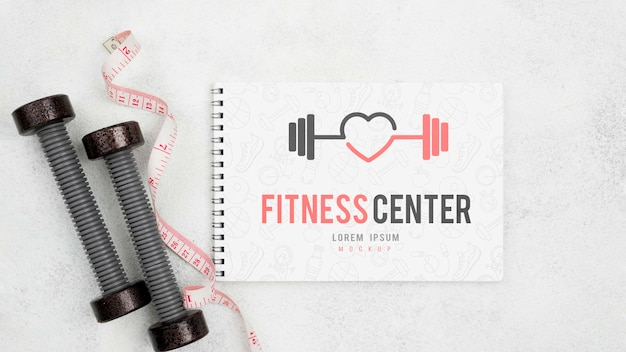 Flat lay of fitness notebook with weights and measuring tape