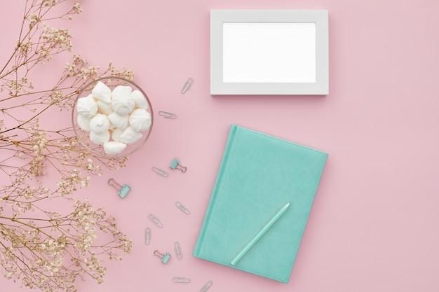 Плоские кладут цветы и дневник на розовый стол, вид сверху. макет