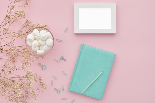 Flat lay flowers and a diary on pink table, top view. mockup