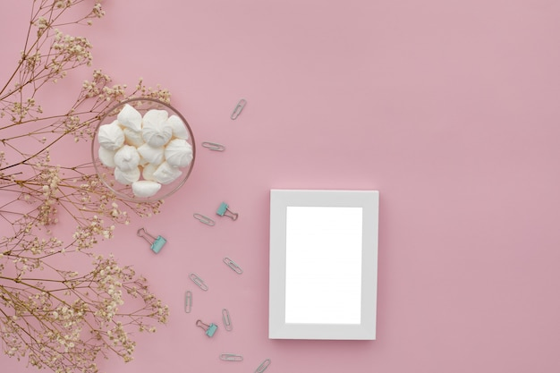 Flat lay flowers, photo frame on pink table
