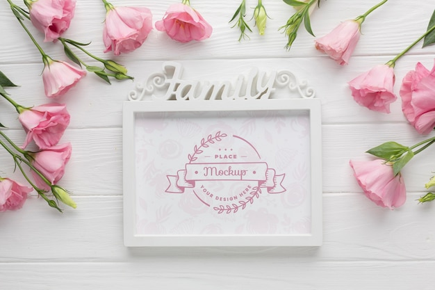 Flat lay of frame with pink roses