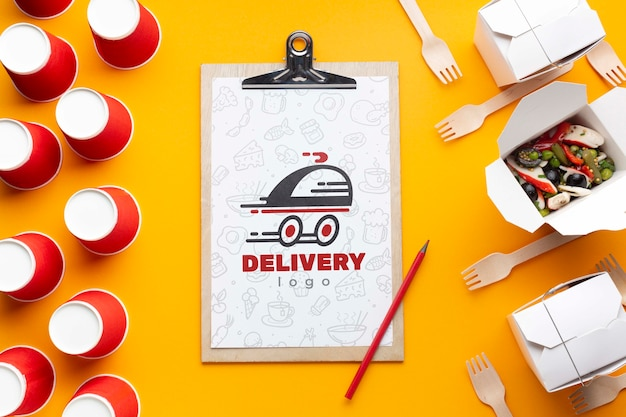 Flat lay free food delivery arrangement with clipboard mock-up