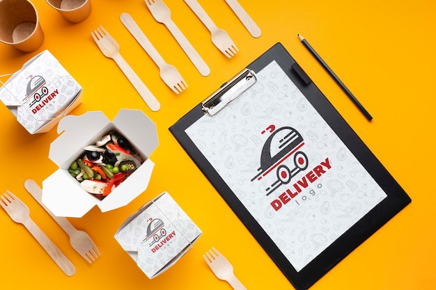 Flat lay free food delivery composition with clipboard mock-up