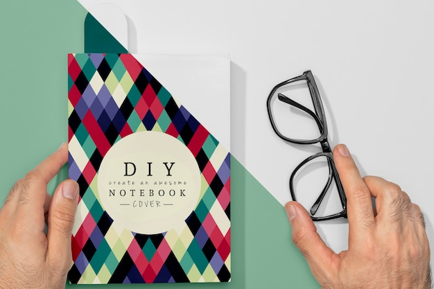 Flat lay hand holding book mock-up and glasses