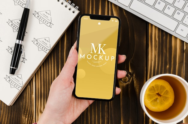 Flat lay hand holding smartphone mock-up with tea on desk