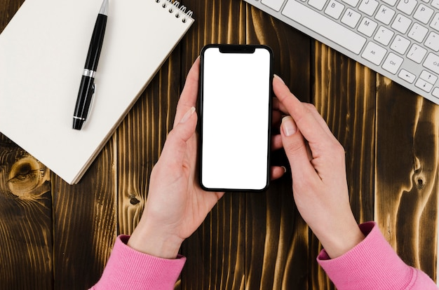 Flat lay hands holding smartphone mock-up with notepad