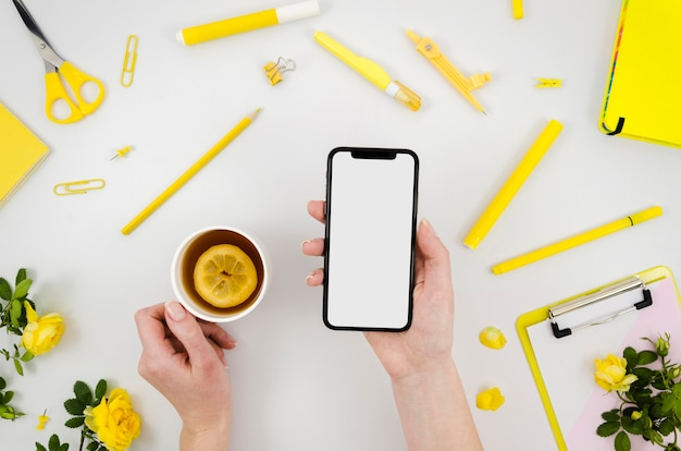 Flat lay hands holding smartphone mock-up with stationery