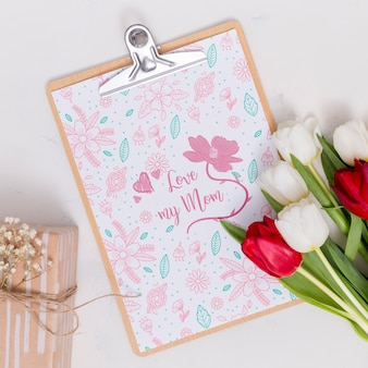 Flat lay mothers day composition with clipboard mockup