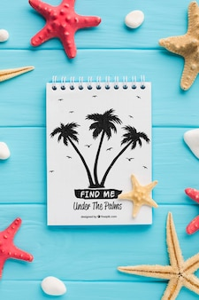 Flat lay notepad with palm trees and starfishes