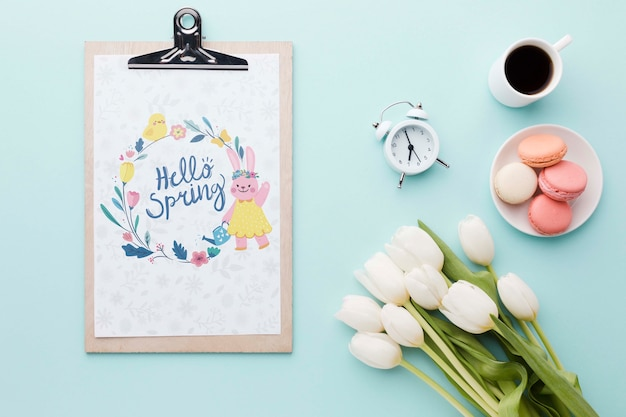 Flat lay of notepad with tulips and macarons