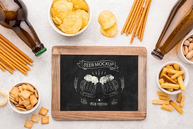 ビール瓶と軽食の品揃えと黒板のフラットレイ