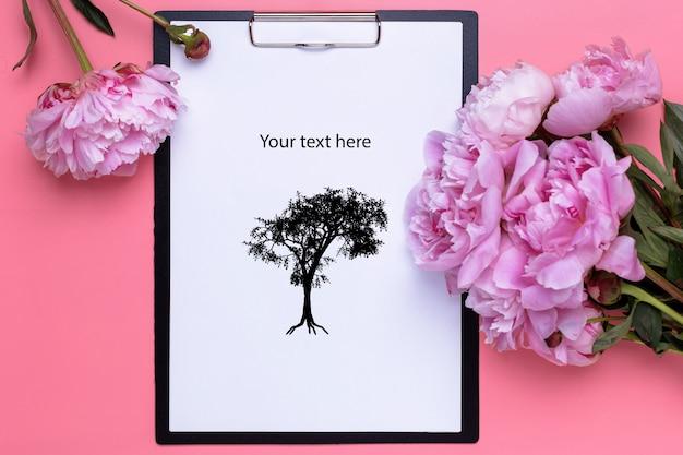 분홍색에 모란의 꽃다발과 클립 보드의 평면 배치
