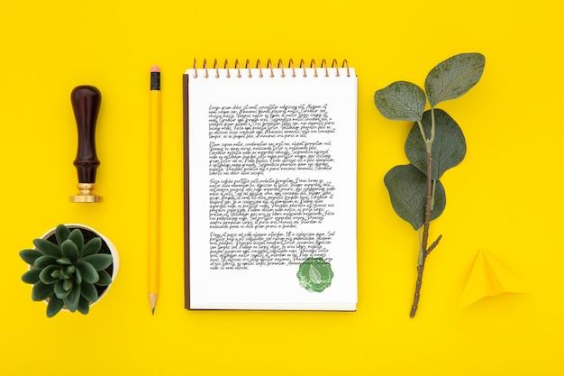 ノートと葉の机の表面のフラットレイアウト