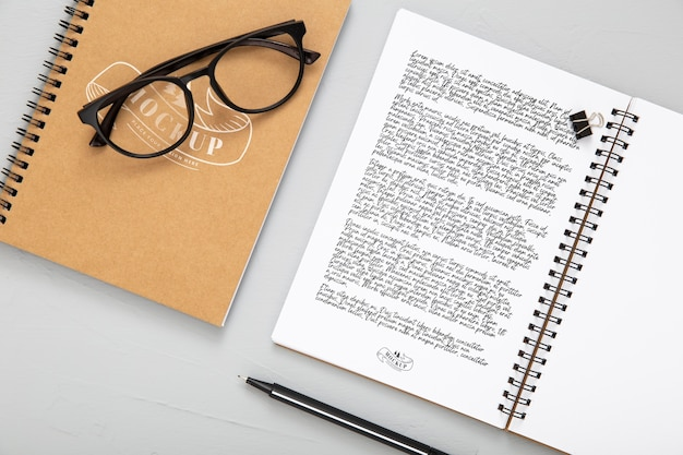 ノートとメガネを置いた机の表面のフラットレイアウト