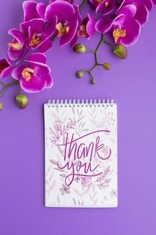 紫色の背景にノートブックモックアップのフラットレイアウト