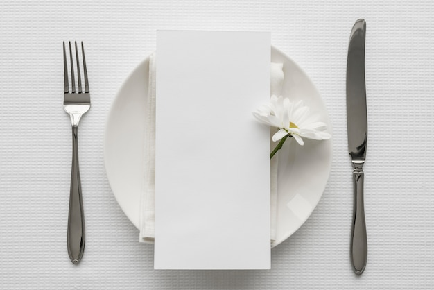 Плоский макет весеннего меню на тарелке со столовыми приборами и цветком