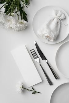 春のメニューのモックアップとカトラリーを備えたテーブルアレンジメントのフラットレイ