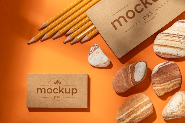 Flat lay of paper stationery with pencils and rocks
