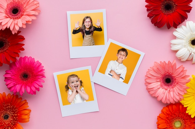 Flat lay of photos and flowers with pink background