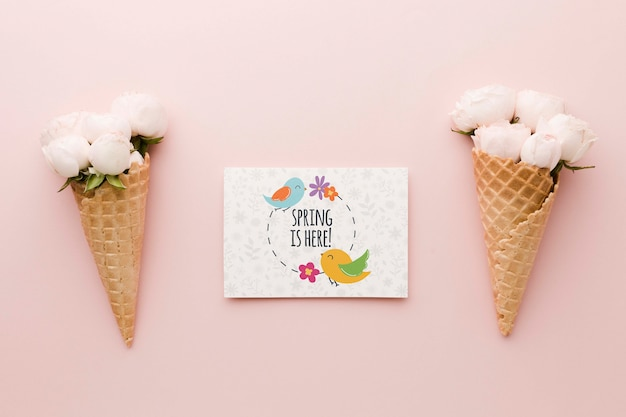 Flat lay of roses in ice cream cones with card