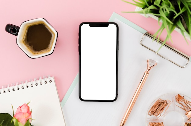 Flat lay smartphone mock-up on clipboard with coffee