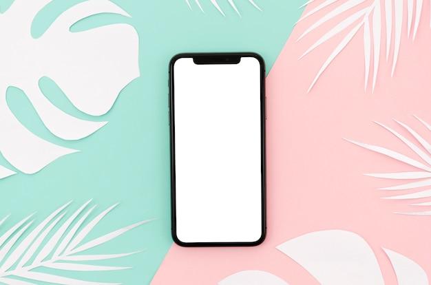 Плоский макет смартфона с листьями на столе