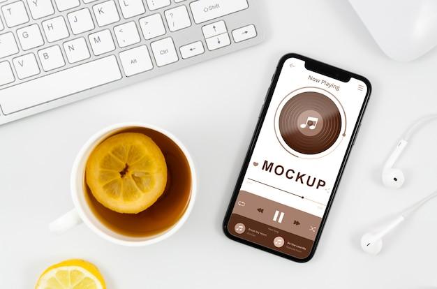 机の上にお茶を置いたフラットレイアウトのスマートフォンモックアップ