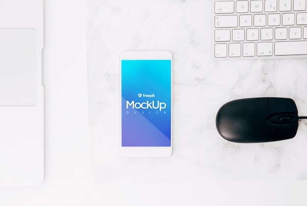 Flat lay smartphone mockup on workspace