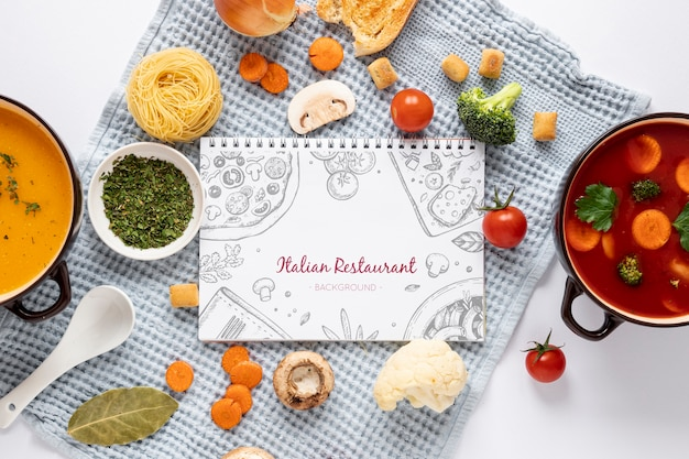 Flat lay soup with assortment of ingredients and notepad mock-up